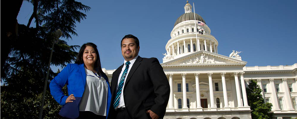 Two people in work attire posing 在 front 的 日e California State Capitol