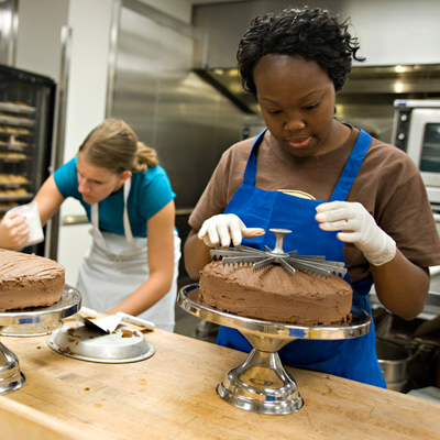 Two students work in the bakery section of the Student Coffee House